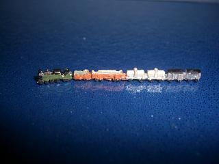 steam locomotive with mixed freight wagons painted green loco
